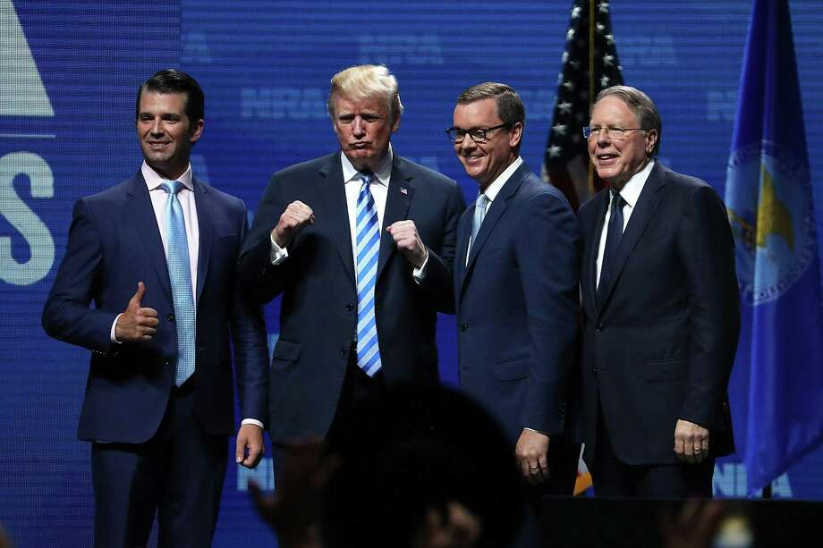 Donald Trump Jr. (from left), President Donald Trump, Executive Director NRA-ILA Chris Cox and NRA Executive Vice President Wayne LaPierre greet the crowd Friday at the NRA-ILA Leadership Forum during the NRA Annual Meeting & Exhibits at the Kay Bailey Hutchison Convention Center in Dallas. Photo: Justin Sullivan /Getty Images / 2018 Getty Images