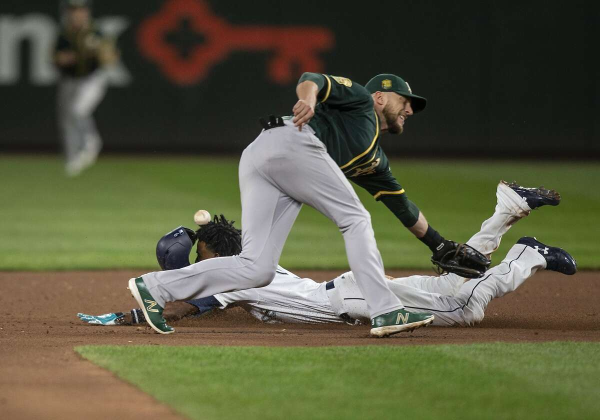 SEATTLE, WA - MAY 3: Dee Gordon #9 of the Seattle Mariners steals second base as second baseman Jed Lowrie #8 of the Oakland Athletics cannot hold on to the ball during the seventh inning of a game at Safeco Field on May 3, 2018 in Seattle, Washington. The Mariners won the game 4-1. (Photo by Stephen Brashear/Getty Images)