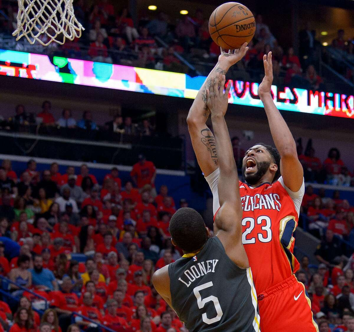 New Orleans Pelicans forward Anthony Davis (23) shoots over Golden State Warriors forward Kevon Looney (5) during the first half of game 3 of the conference semifinal NBA playoffs at the Smoothie King Center in New Orleans, La. Friday, May 4, 2018.