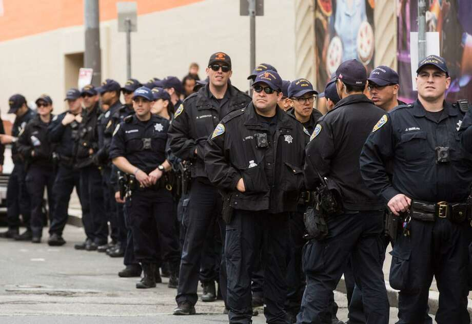 Lines of SFPD officers stand in the street on Saturday, March 24, 2018 in San Francisco. Photo: Jessica Christian / The Chronicle