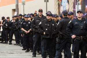 Lines of SFPD officers stand in the street on Saturday, March 24, 2018 in San Francisco.