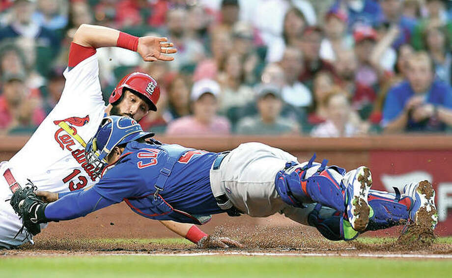 The Cardinals' Matt Carpenter (13) eludes the tag from Cubs catcher Willson Contreras and slides safely into home in the first inning of Friday's game at Busch Stadium. Photo:       AP