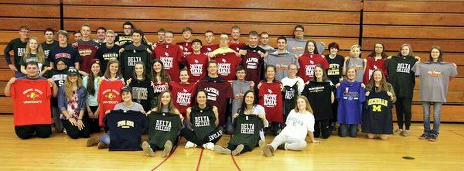 Ubly High School celebrated College Decision Day on Friday, where the 2018 senior class talked about where they were going to continue their educations next year, or what their future plans entailed. The senior class, pictured here, poses with shirts or hats from the schools that they plan on attending. The event was sponsored by: Portrait Expressions by Janel, Northstar Bank, Ubly Motor Service, Fucianari Family Dentistry and Moments Captured by Vanessa. (Mike Gallagher/Huron Daily Tribune)
