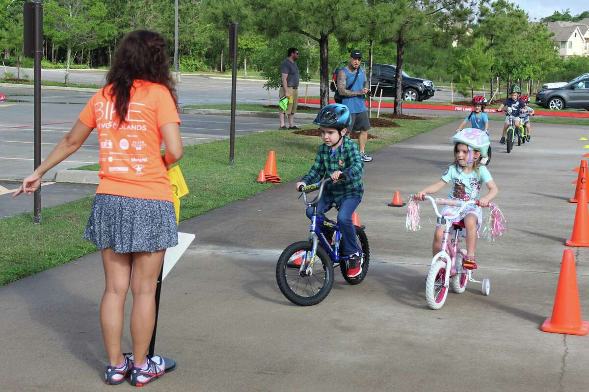 Fernanda Suarez, with Bike The Woodlands Coalition, leads children on a walk through demonstration of the bicycle course during the Kids Bike Rodeo on Saturday, May 5.