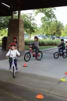 Children learn about safety while riding along the bicycle course during the Kids Bike Rodeo in The Woodlands on May 5, 2018.