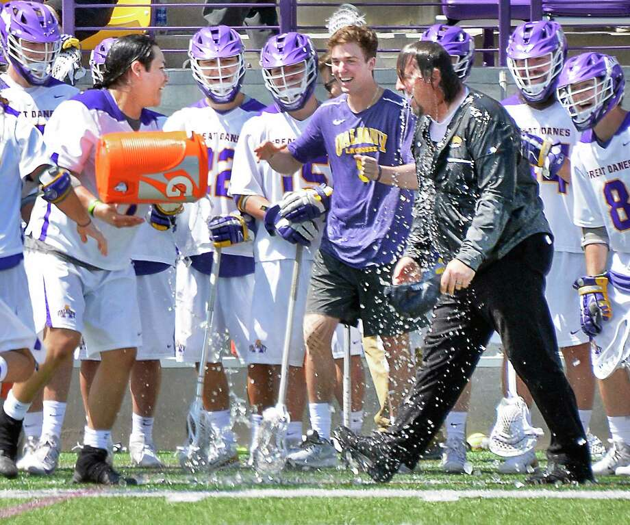 UAlbany's Tehoka Nanticoke, left, drenches head coach Scott Marr with Gatorade as sidelined Connor Fields, center, watches as Albany defeats Vermont for the America East lacrosse championship Saturday May 5, 2018 in Albany, NY.  (John Carl D'Annibale/Times Union) Photo: John Carl D'Annibale, Albany Times Union / 20043706A