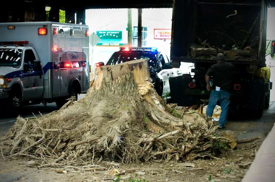 A tree stumps sits in the middle of Elm Street after it fell  a city truck as it got caught under the overpass in Stamford, Conn. on Thursday, July 1 2010. Photo: Kathleen O'Rourke / Stamford Advocate