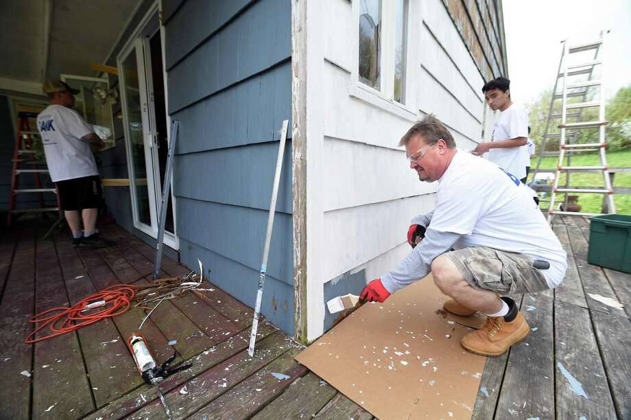Kyle Habiniak (right) of Northford paints a back wall at the home of Brenda Shuler and her three children in Northford as part of HomeFront Day on May 5, 2018.  Volunteers from St. Ambrose Parish painted the exterior and interior, replaced doors and windows, performed siding repairs and electrical work at the home.  This was one of 70 homes throughout Connecticut and Westchester County, New York, that were revitalized on HomeFront Day. Photo: Arnold Gold / New Haven Register / New Haven Register