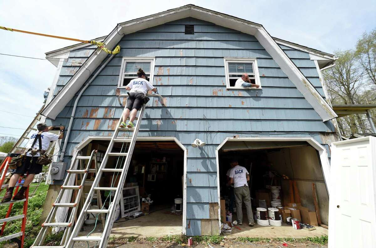 Andrea Konesky (on ladder in center) of Northford scrapes paint on a side wall above the garage at the home of Brenda Shuler and her three children in Northford as part of HomeFront Day on May 5, 2018. Volunteers from St. Ambrose Parish painted the exterior and interior, replaced doors and windows, performed siding repairs and electrical work at the home. This was one of 70 homes throughout Connecticut and Westchester County, New York, that were revitalized on HomeFront Day.