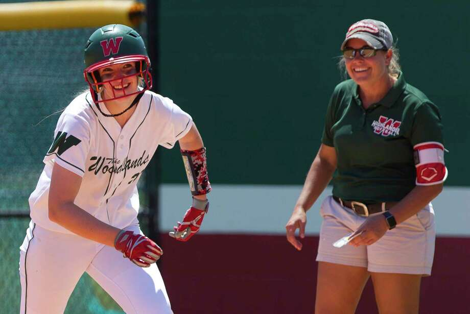 Amanda Curran #22 of The Woodlands jokes with first base coach Paula Miller after hitting a single during a Region II-6A bi-district playoff series, Saturday, April 28, 2018, in The Woodlands. Photo: Jason Fochtman, Staff Photographer / © 2018 Houston Chronicle