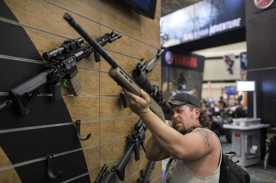 A man examines firearm accessories at a booth at the National Rifle Association Convention, in Dallas, May 4, 2018. The four-day convention, which drew roughly 75,000 attendees from across the United States, brought in NRA members, protesters and even the Democratic mayor of Dallas. (Tamir Kalifa/The New York Times) Photo: TAMIR KALIFA, STR / NYT / NYTNS