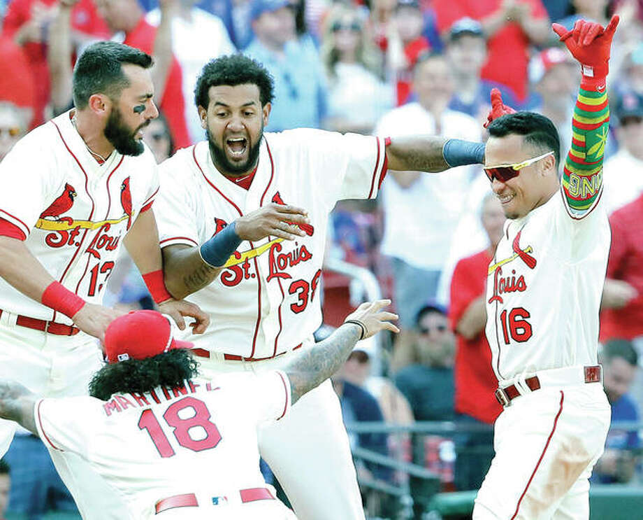 The Cardinals' Kolten Wong (16) celebrates his walkoff home run with teammates Carlos Martinez (18), Jose Martinez (38) and Matt Carpenter in the 10th inning of Saturday's 8-6 win over the Cubs at Busch Stadium. Photo:       AP