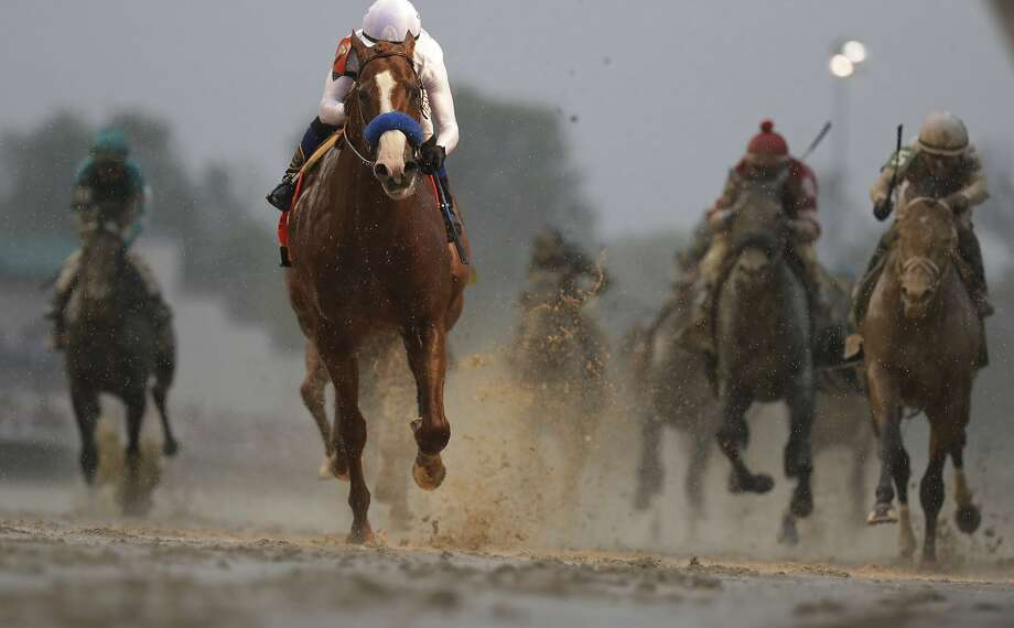 Mike Smith rides Justify to a Kentucky Derby victory through the mud at at Churchill Downs. Photo: Morry Gash / Associated Press