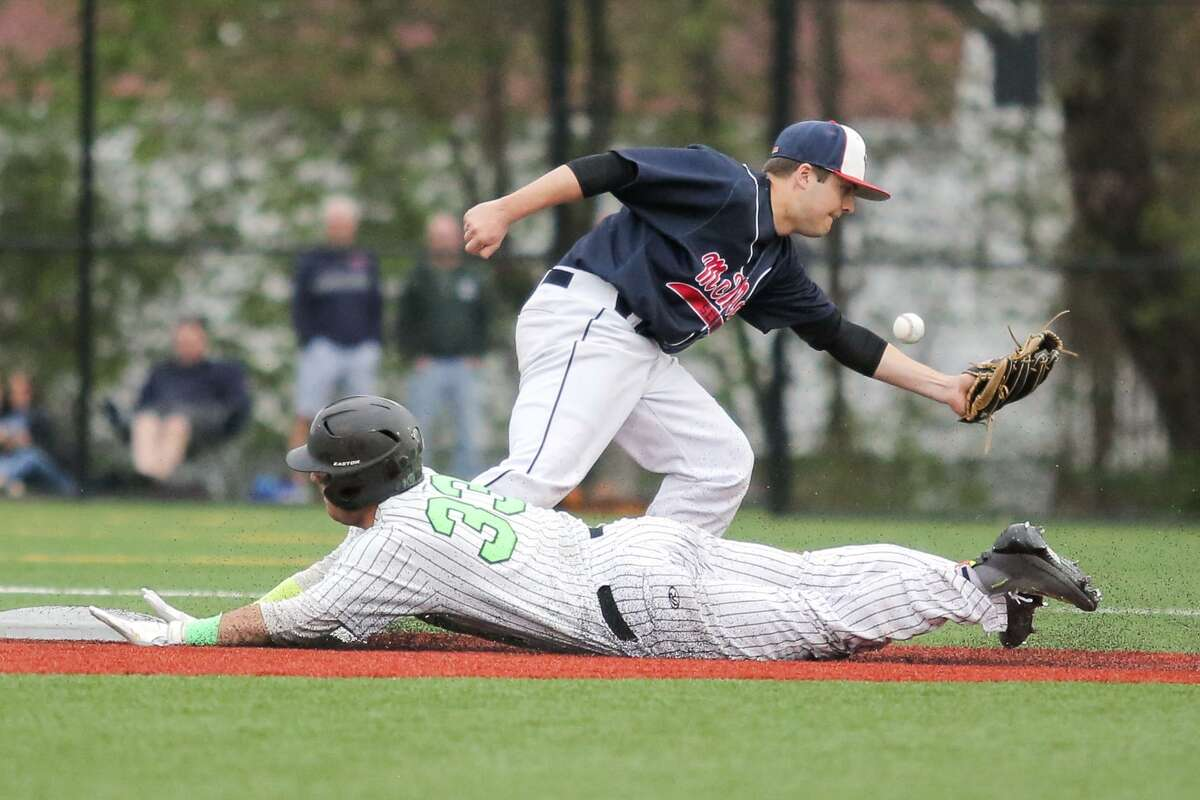 Norwalk's Mario Montiero slides safely into second base after a wild throw during Saturday's game against McMahon.