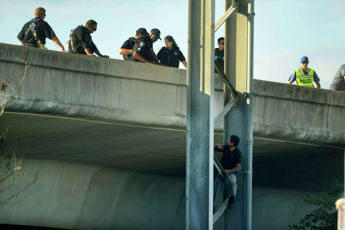 A man sits on a girder off of I-35 North at South Laredo Street in San Antonio on Saturday, May 5, 2018. Bystanders said that he had climbed onto a Transguide sign at about 2 p.m. He finally climbed down on his own at about 6:30 and was immediately taken by police.