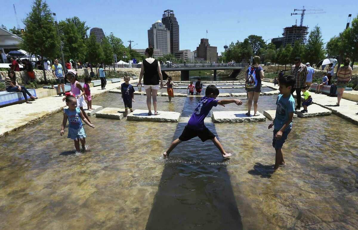Children play in the water at the grand opening Saturday of San Pedro Creek and its new linear park called San Pedro Creek Culture Park. The event included music, children's activities and historical presentations, as well as an evening Illumination ceremony.