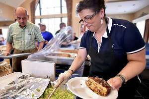 Renee Efthymiou prepares a pastitsio dinner for John Panagos, of Branford at 'A Taste of Greece' at Saint Barbara Greek Orthodox Church, Saturday, May 4, 2018, at 480 Racebrook Road in Orange.