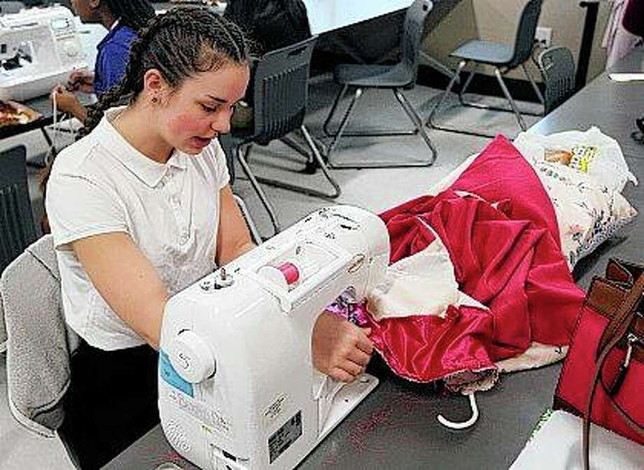 "Student Brigid Duesterhaus operates a sewing machine while making her own prom dress during a sewing class at MacArthur High School in Decatur. ""I just love fashion and designing,"" Duesterhaus said. Photo:       Jim Bowling 