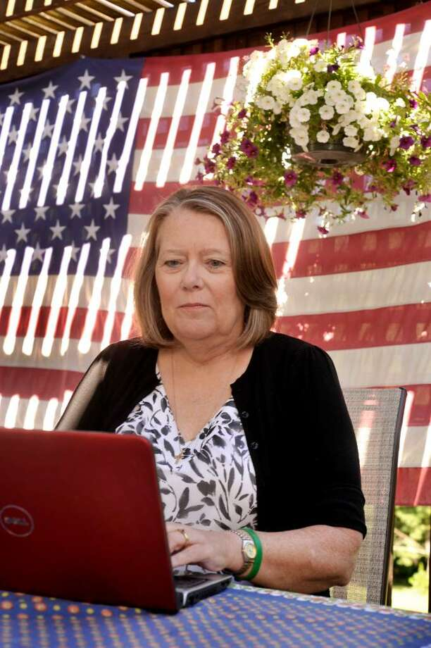Kim Polhemus, 56, works with a laptop computer on the porch of her New Milford home on Friday, July 2, 2010. Kim is looking for a kidney donation. Photo: Michael Duffy / The News-Times