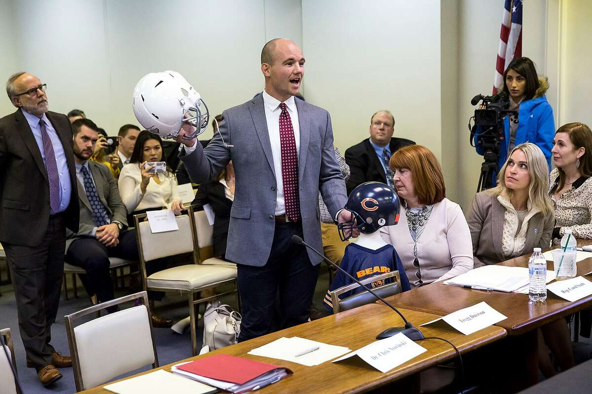 FILE - In this March 1, 2018, file photo, Chris Borland, a former NFL linebacker and Big Ten Defensive Player of the Year at Wisconsin, testifies before the Illinois House Mental Health Committee hearing on House Bill 4341, which would ban tackle football for kids under 12 years of age, in Springfield, Ill. Borland was illustrating how repetitive sub-concussive hits that begin when children play impact sports can be as dangerous as a single hit that results in a concussion. Borland is raising money and awareness for the issue of veterans with traumatic brain injuries by taking part this week in