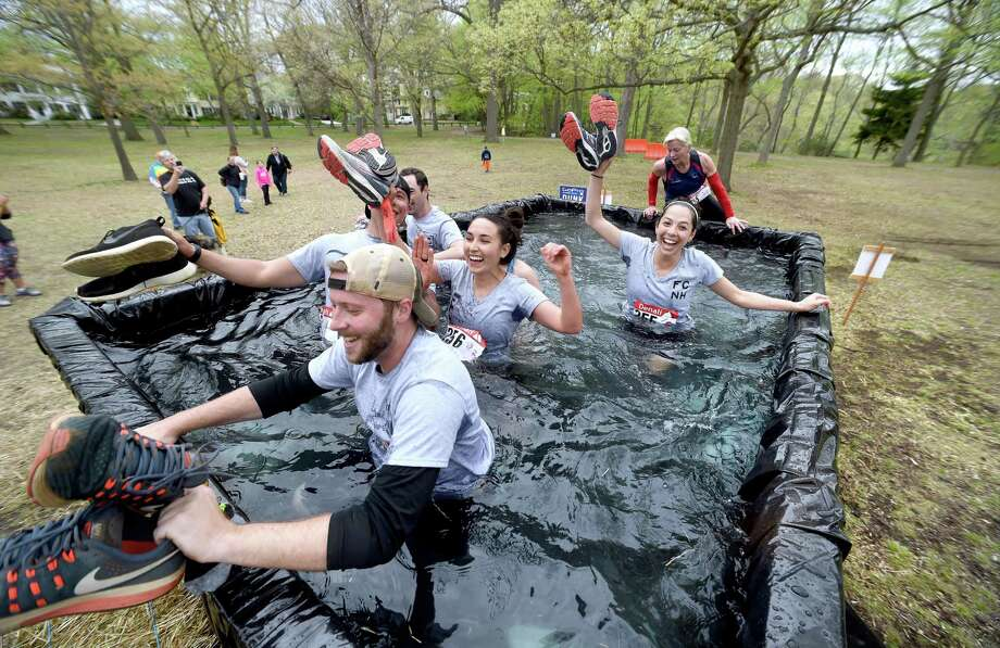 A group of runners in the 2018 Denali Run the Gauntlet East Rock 5K Obstacle Race wade through the GoPro Dunk obstacle in East Rock Park in New Haven on May 6, 2018. Photo: Arnold Gold / New Haven Register / New Haven Register