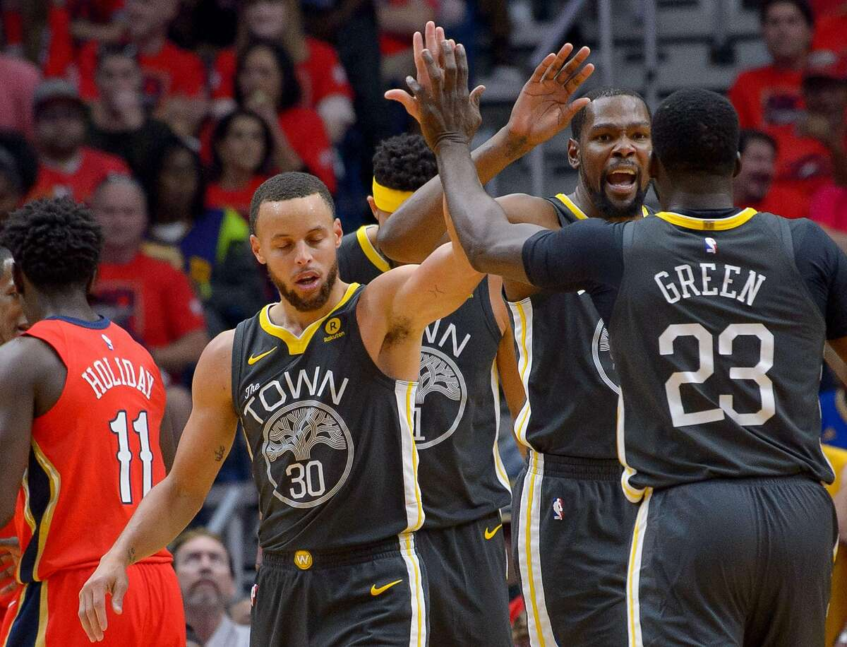 Golden State Warriors guard Stephen Curry (30), Golden State Warriors forward Draymond Green (23), and Golden State Warriors forward Kevin Durant (35) celebrate a play against the New Orleans Pelicans during the first half of game 3 of the conference semifinal NBA playoffs at the Smoothie King Center in New Orleans, La. Friday, May 4, 2018.
