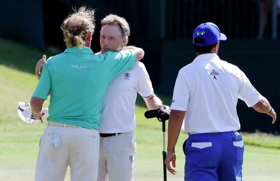 Bernhard Langer, center, hugs his playing partners Miguel Angel Jimenez, left, and Tom Pernice Jr. on the 18th green after Langer won the Insperity Invitational at the The Woodlands Country Club Sunday, May 6, 2018, in The Woodlands, TX. (Michael Wyke / For the  Chronicle) Photo: Michael Wyke, Freelance / © 2018 Houston Chronicle