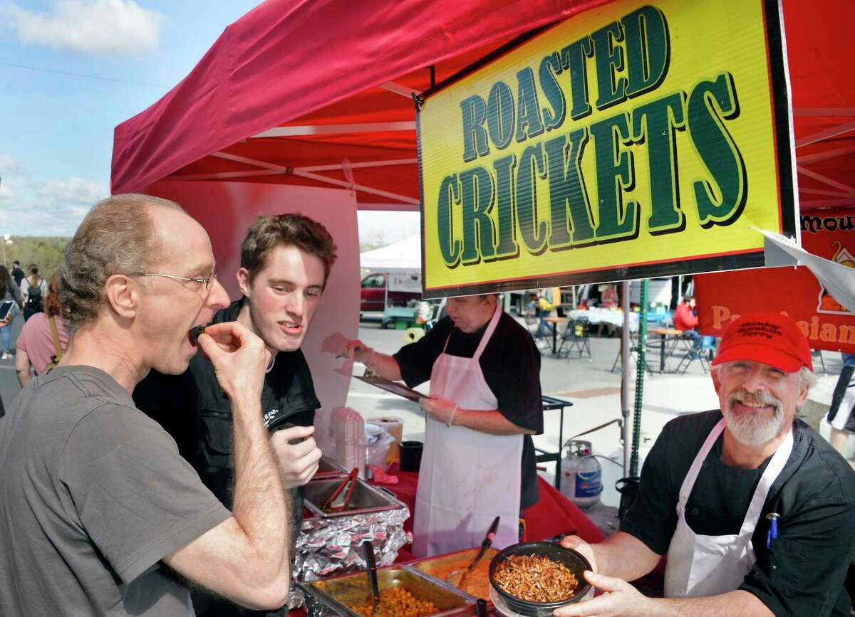 Andrew Ashley, left, of NYC and his nephew James Ashley of Loudonville sample roasted crickets from Mike Gordon's booth as the Troy Waterfront Farmers Market begins its Outdoor Market on River Street Saturday May 5, 2018 in Troy, NY. (John Carl D'Annibale/Times Union)