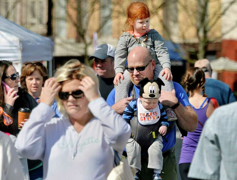 Dan Jackson, center, of Troy carries daughter Lydia, 4, top, and 9-month-old son James through the Troy Waterfront Farmers Market as it begins its Outdoor Market season on River Street Saturday May 5, 2018 in Troy, NY. (John Carl D'Annibale/Times Union)