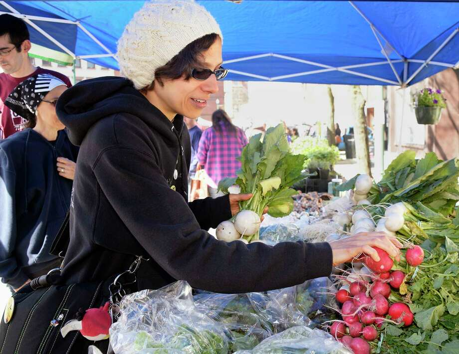 Theresa Houghton, a plant based wellness consultant from North Greenbush, picks out Japanese turnips and radishes as the Troy Waterfront Farmers Market begins its Outdoor Market on River Street Saturday May 5, 2018 in Troy, NY.  (John Carl D'Annibale/Times Union) Photo: John Carl D'Annibale / 40043663A
