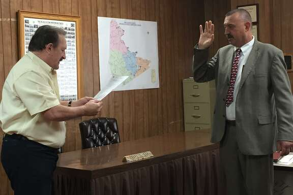 San Jacinto County Pct. 3 Justice of the Peace Randy Ellisor (left) swears in Fritz Faulkner (right) as the interim county judge after a vote by the commissioners court on April 30.