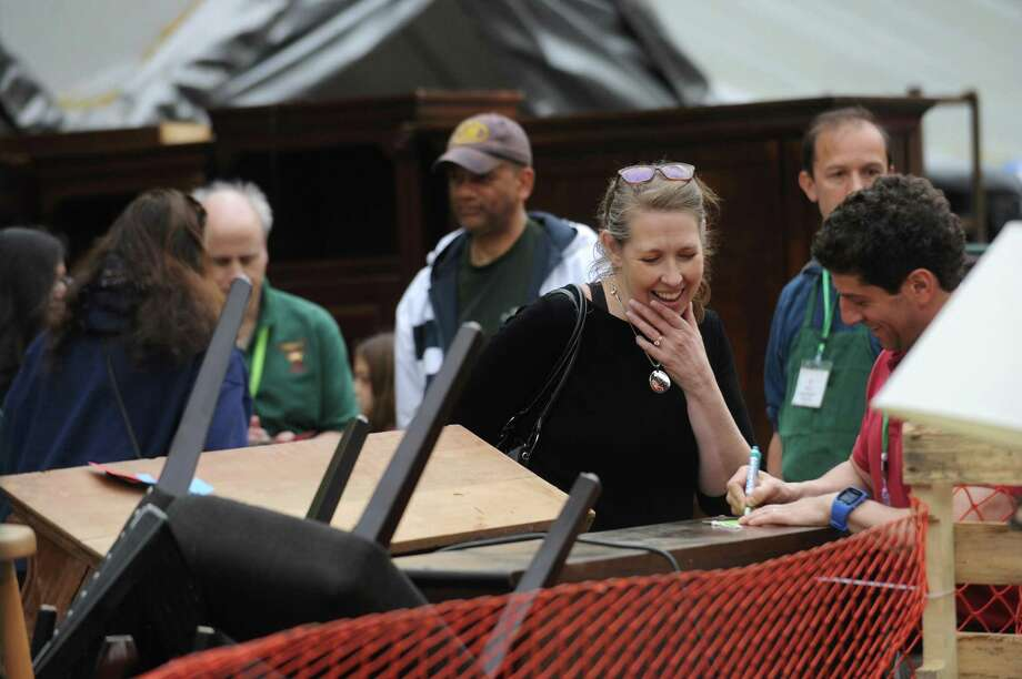 Darien resident Nancy Coughlin smiles as she finalizes a transaction with John Baliotti during the Darien Boys Scouts 46th annual Giant Tag Sale held at the Andrew Memorial Scout Cabin in Darien, Conn. on Sunday, May 6, 2018. Photo: Michael Cummo / Hearst Connecticut Media / Stamford Advocate