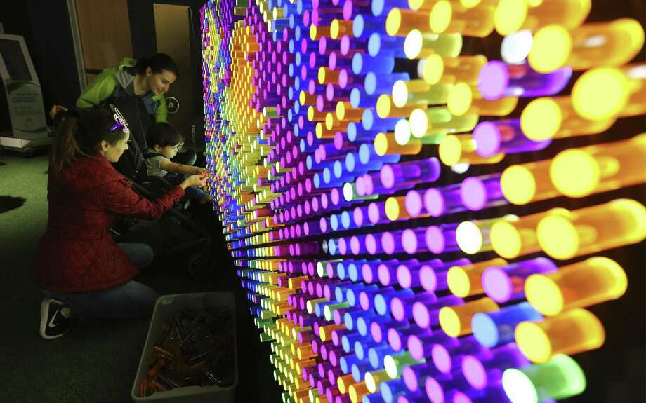 "Claudia Sanchez (left) with her 16-month old child, Enzo Ramos, and Lindsey Peters have fun on a ""lite brite""-type board at one of the Do-Seum's prototype exhibits on Friday, May 4, 2018. The prototypes offer the museum  way to get feedback from patrons - young and older - before including it as part of an exhibit which they are planning for the summer called ""Dream Tomorrow Today."" Area museums around town are open for free as part of the Tricentennial celebration called Arts for All day on Friday, May 4, 2018. The crowds at The DoSeum were a mix of patrons who knew about the free event which is held on behalf of the city's 300th anniversary. (Kin Man Hui/San Antonio Express-News) Photo: Kin Man Hui, Staff / San Antonio Express-News / ©2018 San Antonio Express-News"