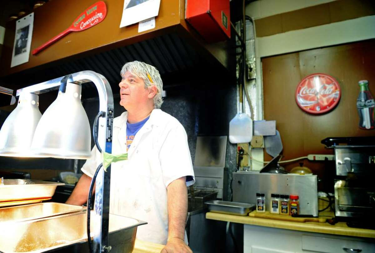 Rory Romeo mans the grill and fryer at his family-run concession stand on Jennings Beach in Fairfield Friday July 2, 2010.