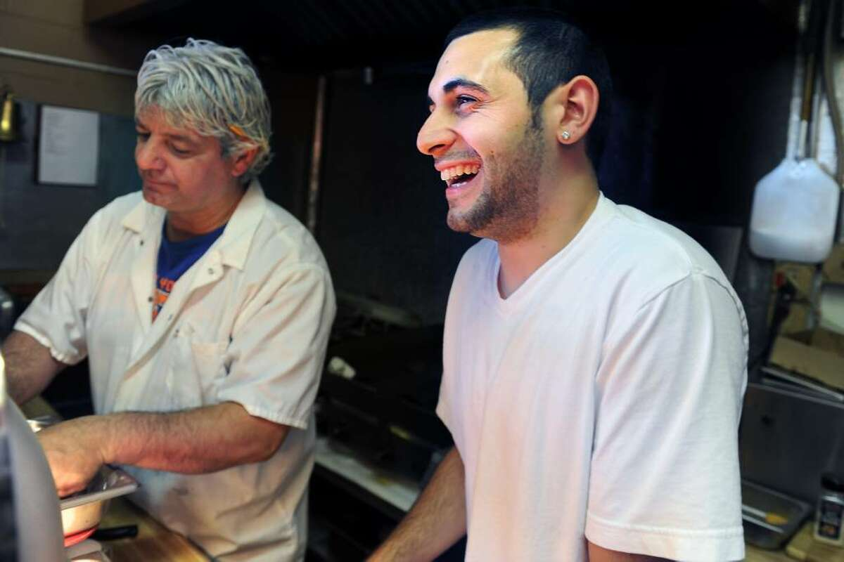 Mike Romeo works alongside his father Rory at their family-run concession stand on Jennings Beach in Fairfield Friday July 2, 2010.