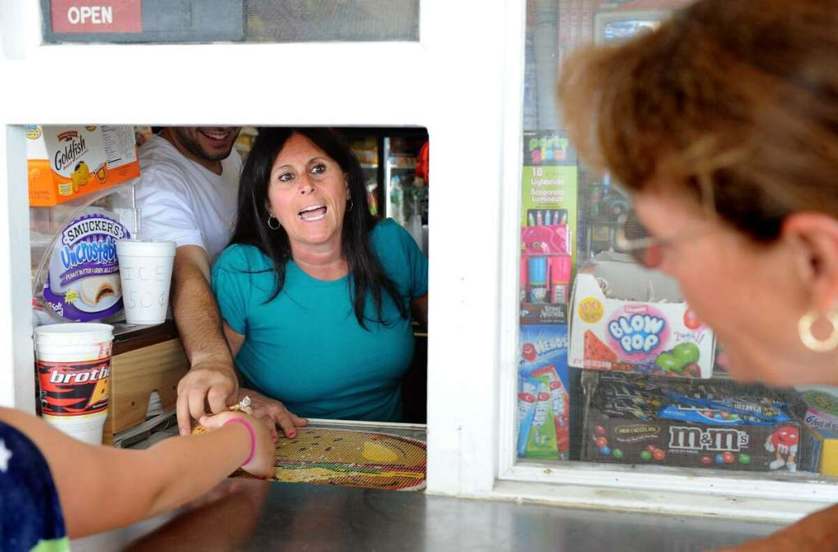 Laura Romeo takes a customer's order as her son Mike reaches over her to pass an ice cream to another customer at their family-run concession stand on Jennings Beach in Fairfield Friday July 2, 2010.