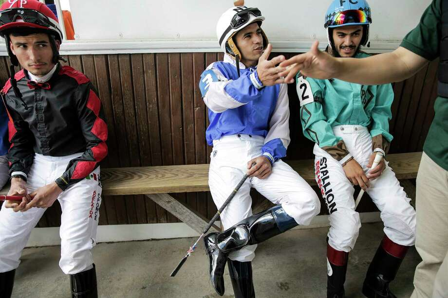 Jockeys Claudio Aguilar, from left, Noe Villatoro and Fransico Calderon wait in the paddock before getting on their horses. Although the horses typically will only compete in one race a day, jockeys will often ride multiple times. Photo: Elizabeth Conley / © 2018 Houston Chronicle