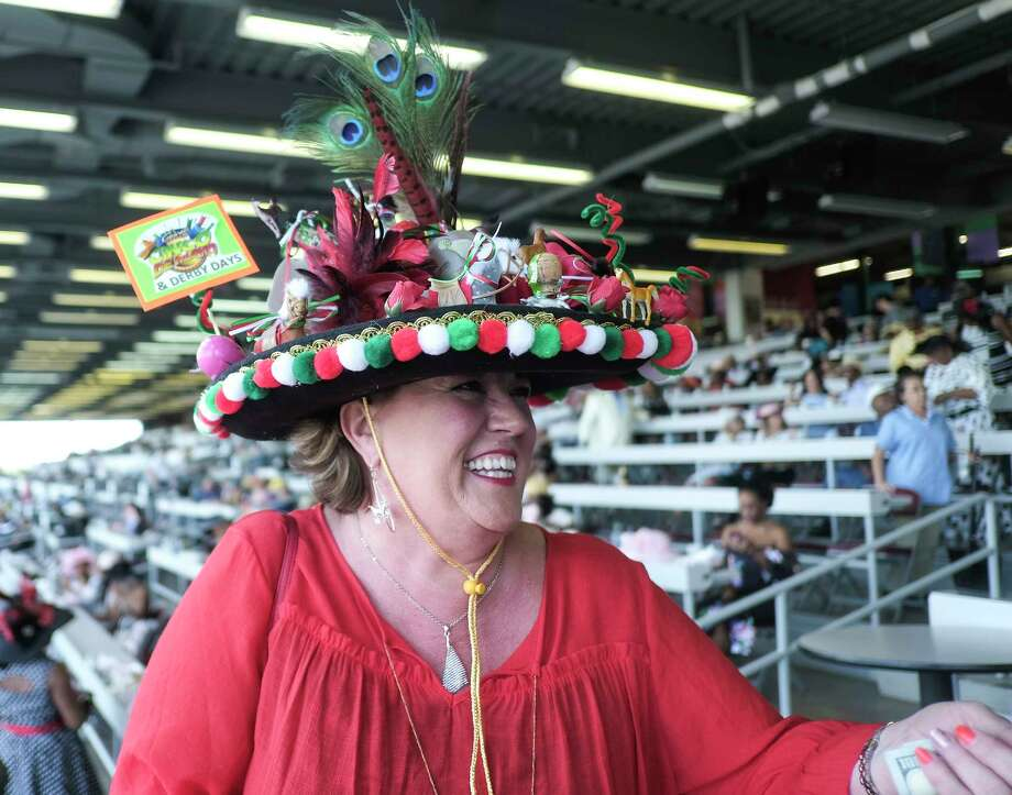 "Jacinda Gispanski laughs after winning $500 during the derby hat contest at the park. ""I mixed together Cinqo de Mayo and the Derby theme: roses, tequilla and horses."" Gispanski said. Last time Gispanski attended she wore a store-bought hat, this year she decided to up her game. Photo: Elizabeth Conley / © 2018 Houston Chronicle"