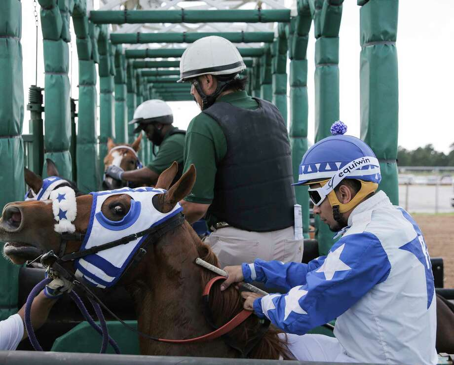 Jockeys line up in the starting gate with their horses and try to keep them calm and focused. Officials try to keep them in the gate as little as possible to keep the horses from getting injured. Photo: Elizabeth Conley / © 2018 Houston Chronicle