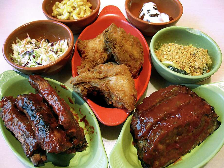 Entrees and sides, clockwise from bottom left: barbecue pork ribs, cole slaw, mac and cheese, candied yams, squash casserole, meatloaf and fried chicken from Paula Deen's Family Kitchen inside Bass Pro Shops at The Rim in San Antonio. Photo: Mike Sutter /San Antonio Express-News
