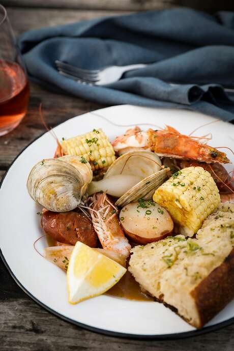 A California clambake with Monterey clams, head-on shrimp, sausage, corn, potatoes and a serving of green garlic bread. Photo: Russell Yip / The Chronicle