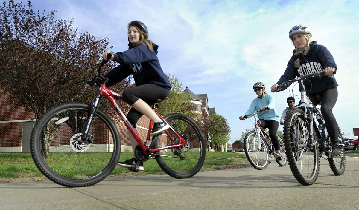 From left, Meghan McNally, 17, Olivia Thalassinos, 18, and Kayla Foster, 17, ride bicycles around New Milford High School Monday morning. The school started a new bike safety initiative where students learn these skills in gym class.