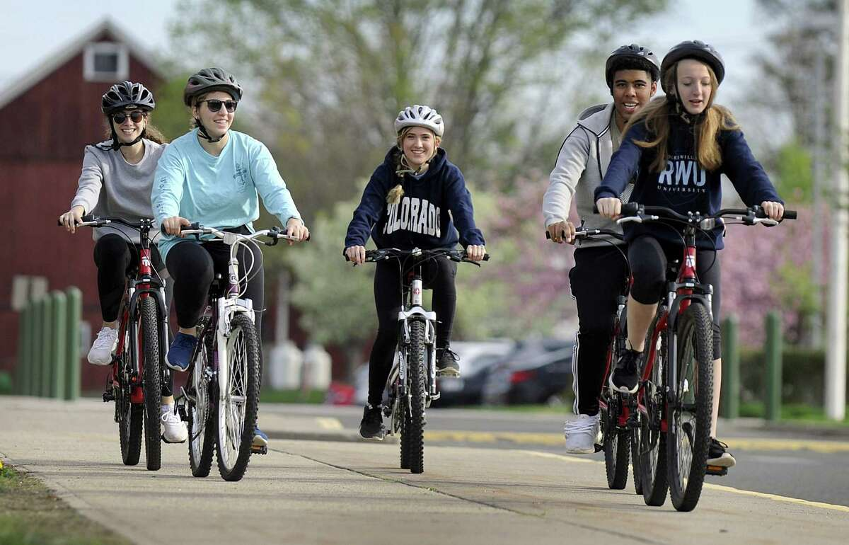 From left, Brianna LeRose, 18, Olivia Thalassinos, 18, Kayla Foster, 17, Ken Echavarria, 18, and Meghan McNally, 17, ride bicycles around new Milford High School Monday morning, May 7, 2018. The school started a new bike safety initiative where students learn these skills in gym class.