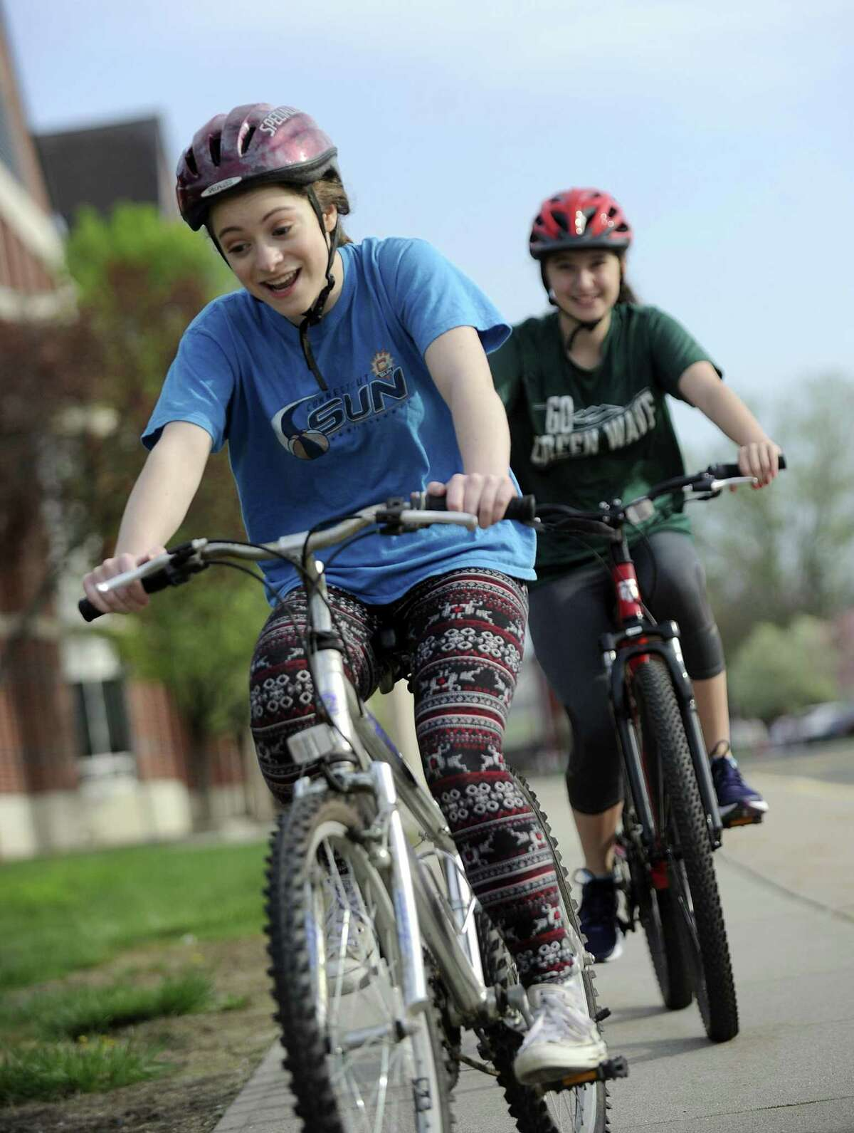 McKenna Riedl, 14, left, and Lilian Vito, 15, ride bicycles around New Milford High School Monday morning. The school started a new bike safety initiative where students learn these skills in gym class.