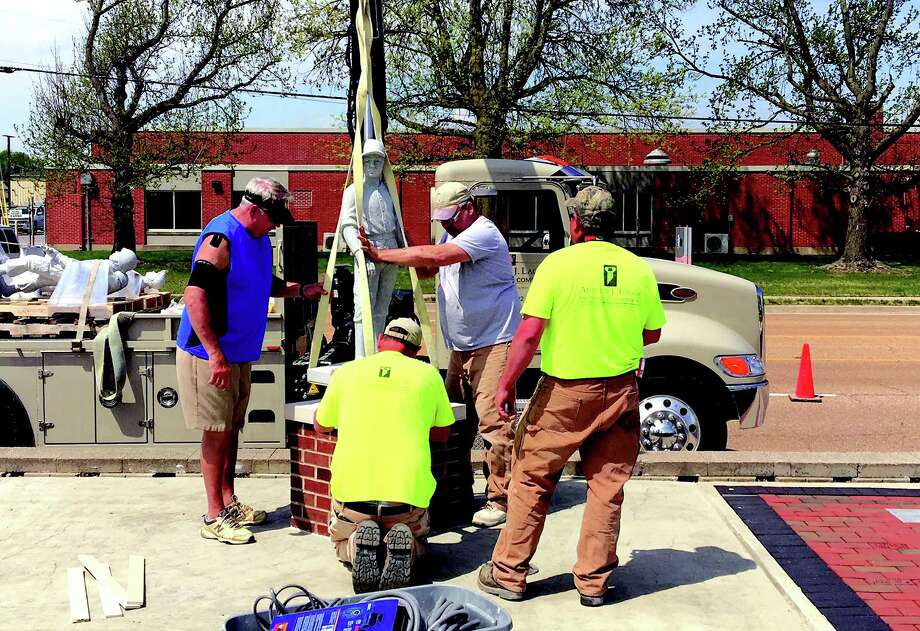 Employees with Lager Monument Company ease the statue of a baseball player onto a pedestal at the Maryville Memorial in the lawn of Village Hall. A total of four statues featuring the baseball player, coal miner, soldier and fireman were installed at the memorial