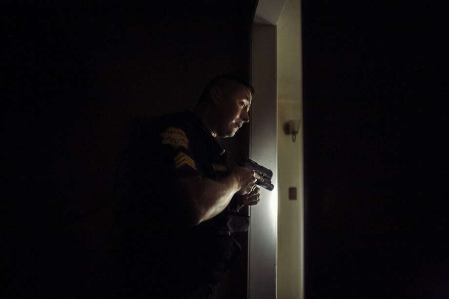 Fresno police Sgt. Paul Cervantes of the Multi Agency Gang Enforcement Consortium conducts a security sweep of a home in Fresno. Photo: Brian L. Frank / Catchlight Fellow / Marshall Project