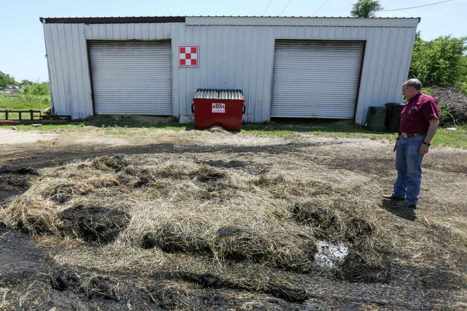 Bill Bergfeld, of Conroe Feeder's Supply, spots a patch of hay that is still smoldering from a fire that was put early that morning on Monday, May 7, 2018, at Conroe Feeder's Supply. Photo: Michael Minasi, Staff Photographer / © 2018 Houston Chronicle