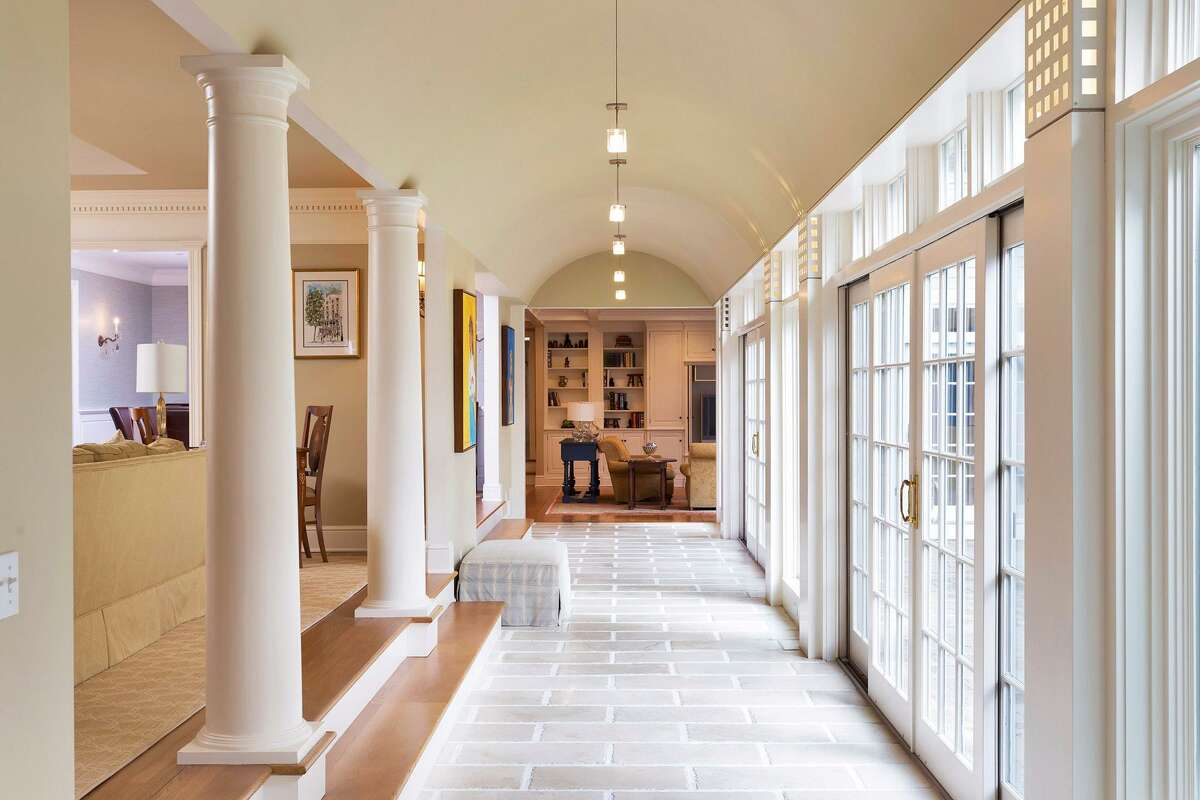Doric columns stand at the rear of the formal living room where there are steps down into the loggia with a barrel vaulted ceiling and sliding doors to the patio and backyard.