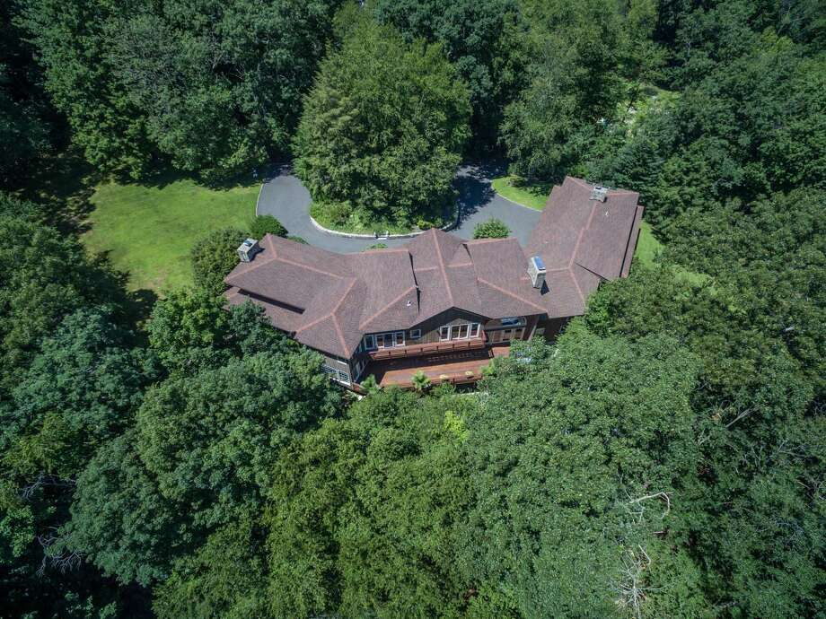 The custom-built contemporary house at 200 Steep Hill Road sits on a 2.42-acre sanctuary-like property in Lower Weston.