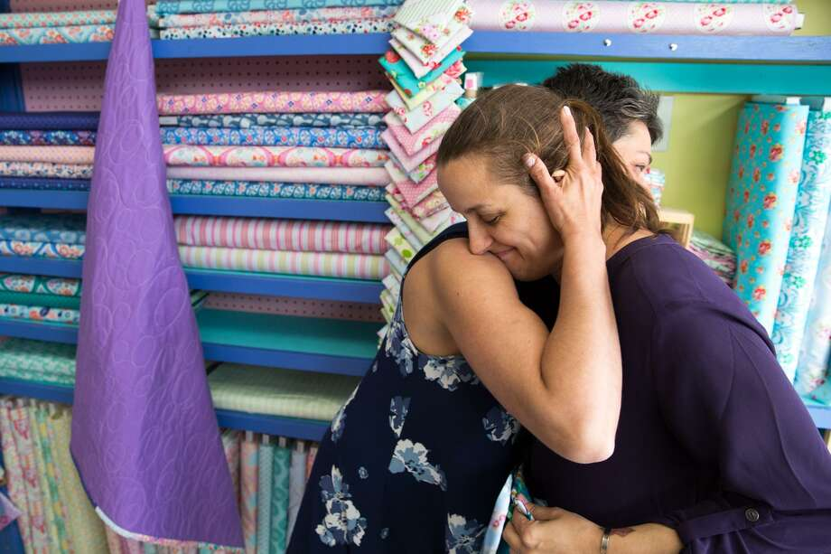 Christy Pugh receives a hug from Christie Ruiz at Christie's Quilting Boutique in Norwalk. Pugh lost her 6-year-old daughter, Emma Mackenzie Splan, to flu complications earlier this year. Quilters gathered together to help Pugh sew quilts for her daughter's classmates and teachers with fabrics donated from around the world. Photo: Chris Palermo / For Hearst Connecticut Media / Norwalk Hour Freelance